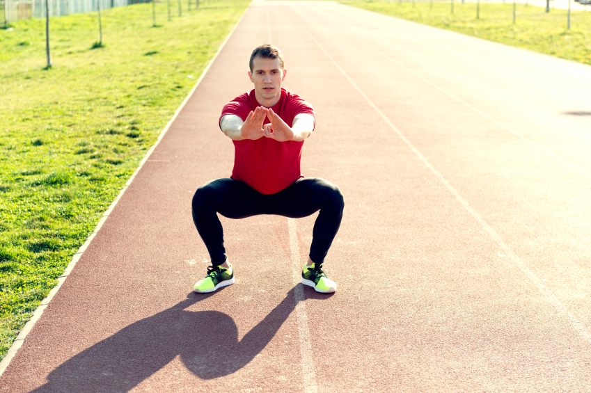 man performing bodyweight squats on a track