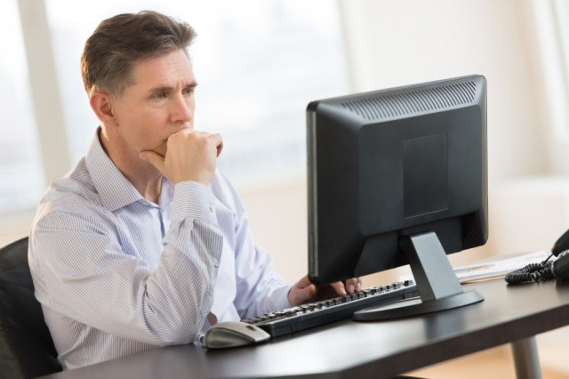 A stressed man sits at his work computer