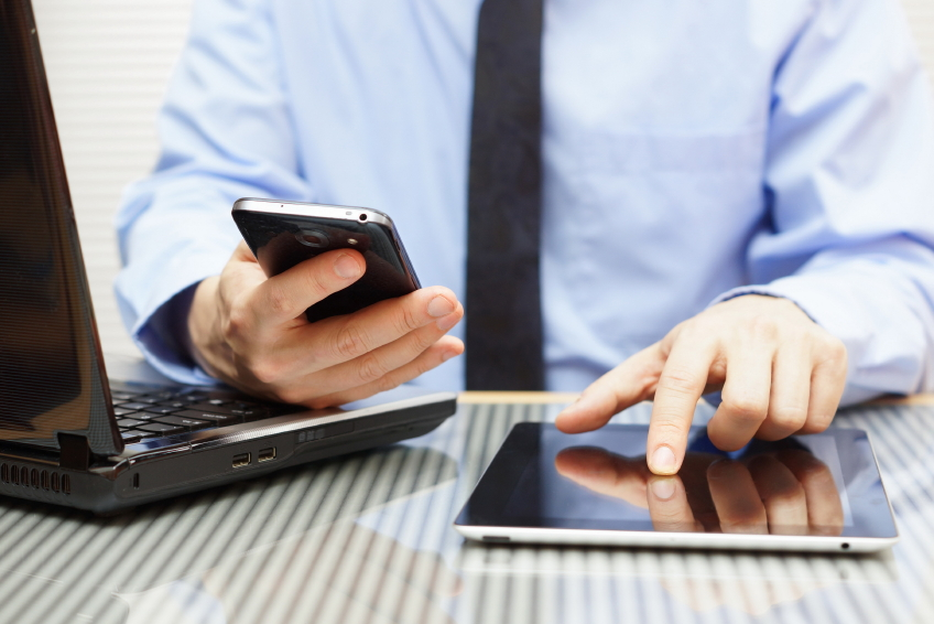 Man using phone, laptop, and tablet