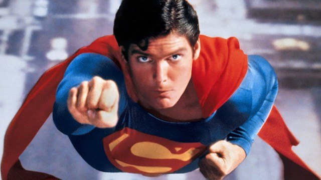 Christopher Reeve with his arm extended, flying through the air as Superman