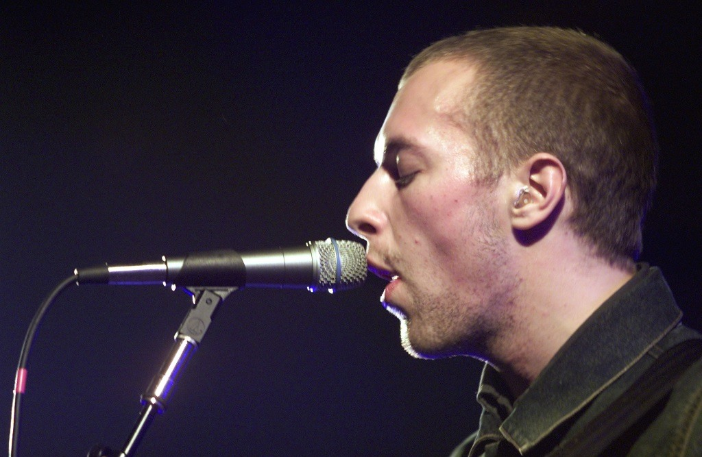 Coldplay lead singer Chris Martin is singing closely to a microphone.
