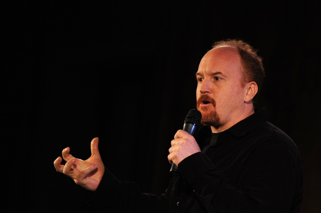 Louis C.K. is talking on stage.