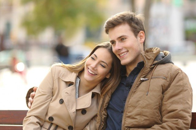 couple sitting on park bench smiling