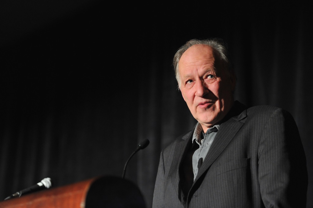 Werner Herzog wearing a suit, looking up and speaking at a podium