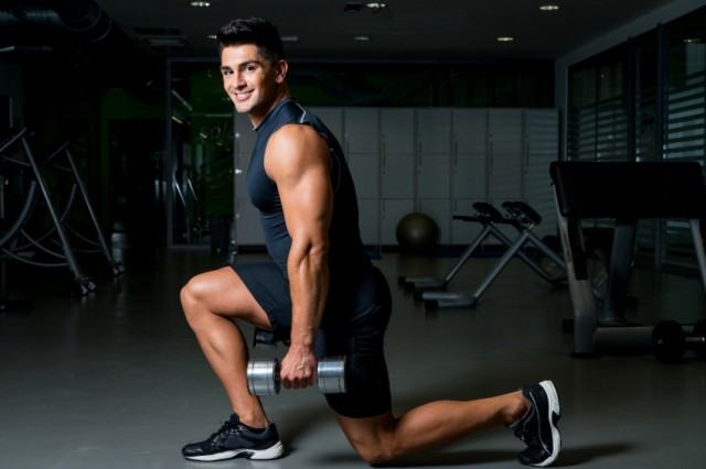 Man lunges with dumbbells