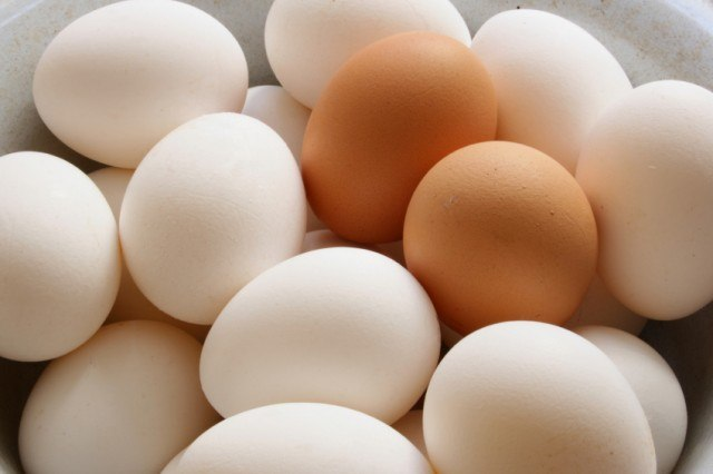 White and brown eggs in a pile.