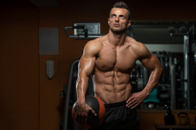muscular man resting with a medicine ball in his hand
