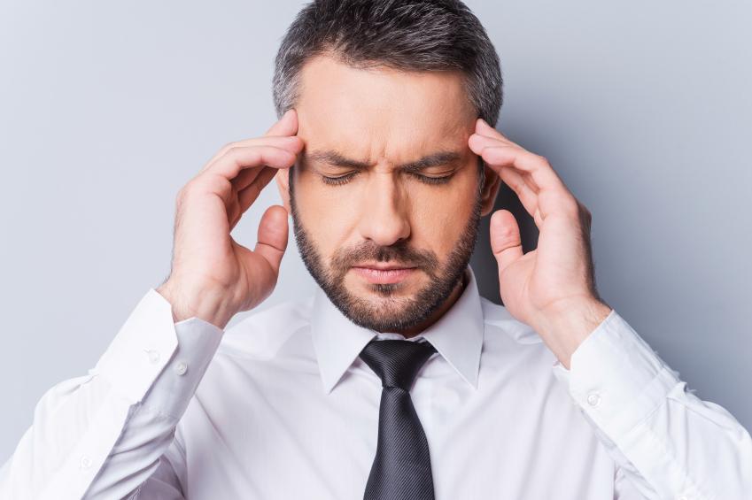 A man feeling a terrible headache