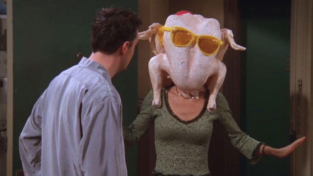 Chandler opening a door to see Monica with a turkey wearing sunglasses on her head.