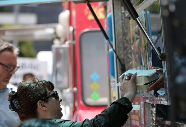 A woman taking a food order from a food truck.