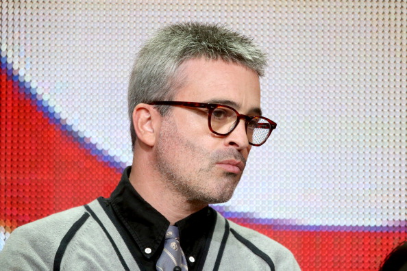 Alex Kurtzman wearing glasses and a tie, looking slightly down and to his left