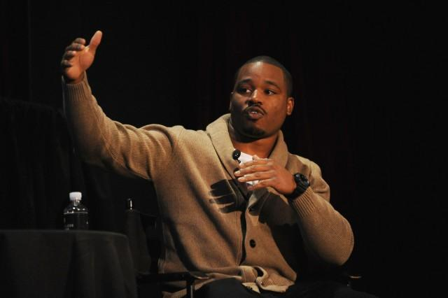 Ryan Coogler speaks at a forum, with his right arm extended up and out