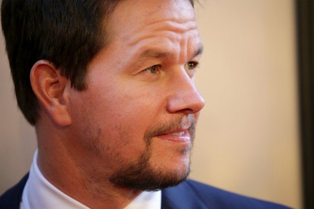 Mark Wahlberg wearing a blue suit, looking to the right of the frame.