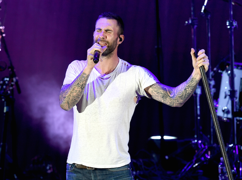 Adam Levine is singing on stage in a white t-shirt.