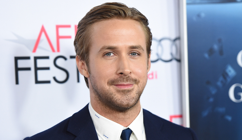 Ryan Gosling smiles in a suit at an event