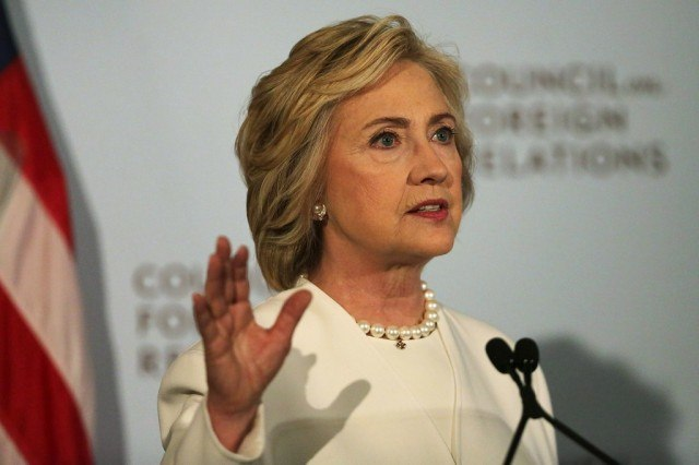Hillary Clinton speaking into a microphone while wearing a white suit and pearls.