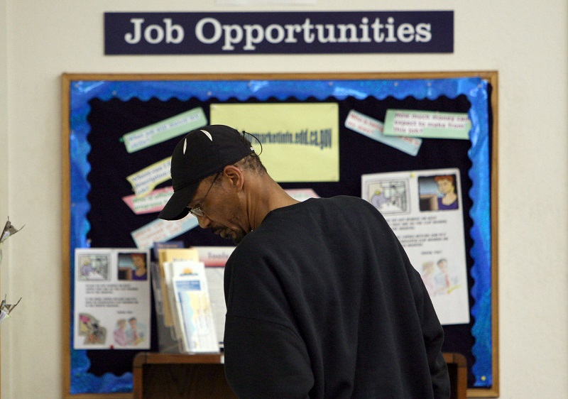 A man stands in front of a job board