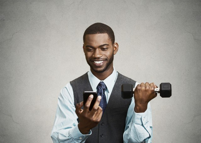 Happy man reading and lifting weights