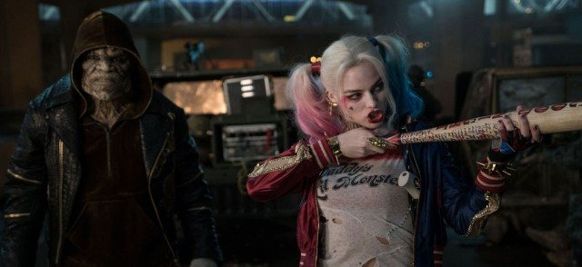 Harley Quinn pointing a bat and making a facial expression.