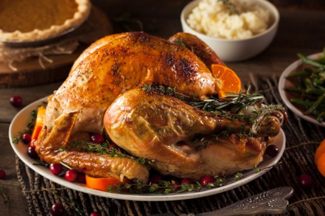 Roasted turkey on a plate with cranberries, mashed potatoes, and pumpkin pie