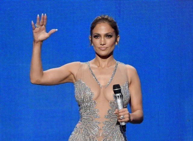 Jennifer Lopez on-stage, with her right hand up.