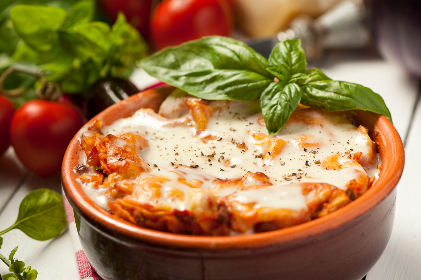 A small bowl of lasagna with fresh herbs
