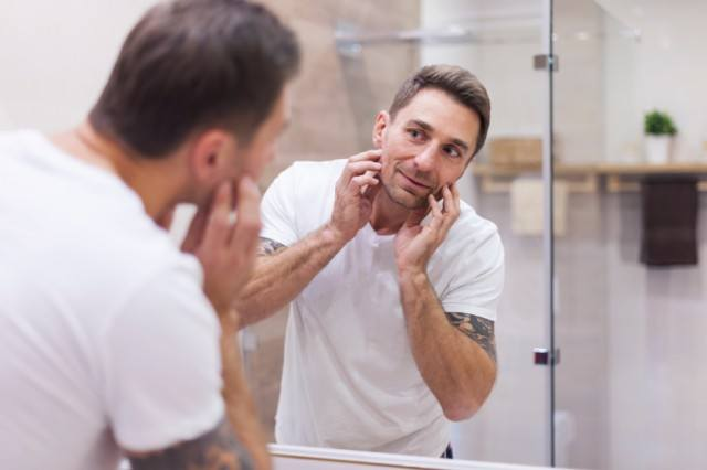 A man looking at his face in a mirror.
