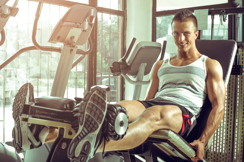 man doing leg extensions in the gym