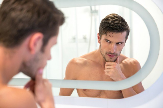 a man looking at himself in the mirror