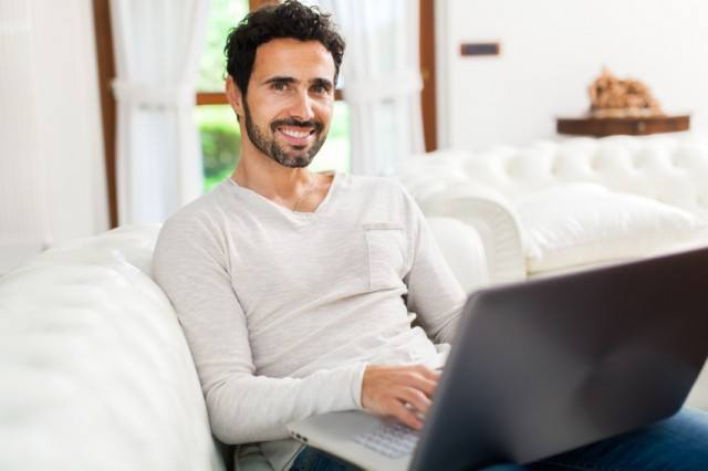 Man smiling and holding his laptop
