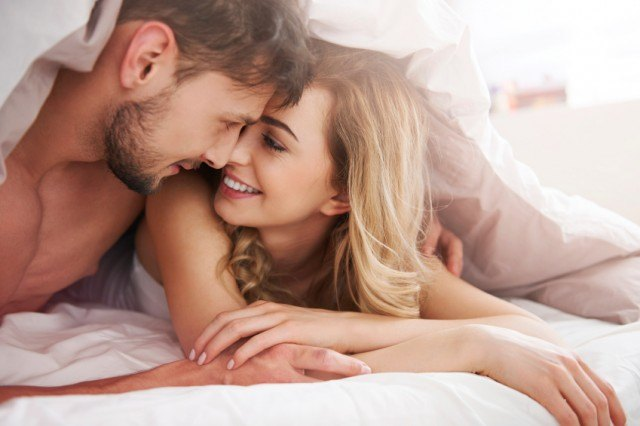 Couple in bed, snuggling under the covers