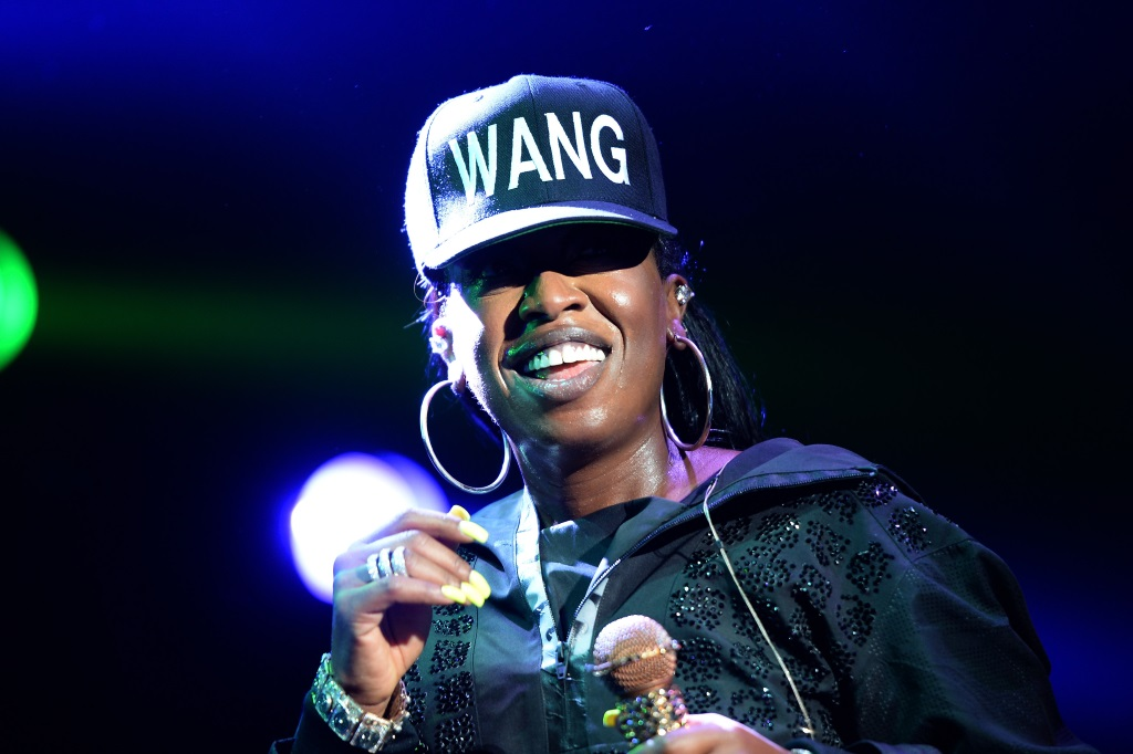 """Missy Elliott is smiling on stage and is wearing a black hat that has the word """"WANG"""" on it."""
