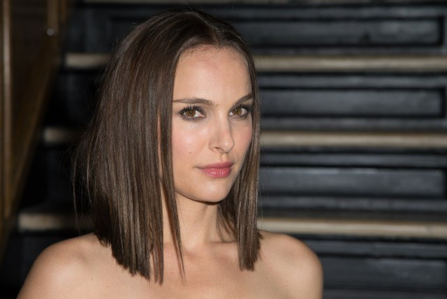 Natalie Portman stands in front of a staircase.