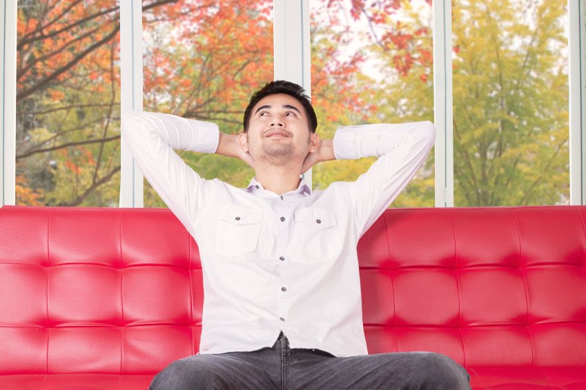Pensive man sitting on sofa while looking up