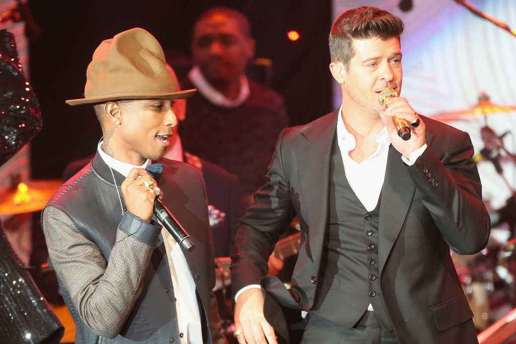 Pharrell Williams and Robin Thicke are singing on stage.