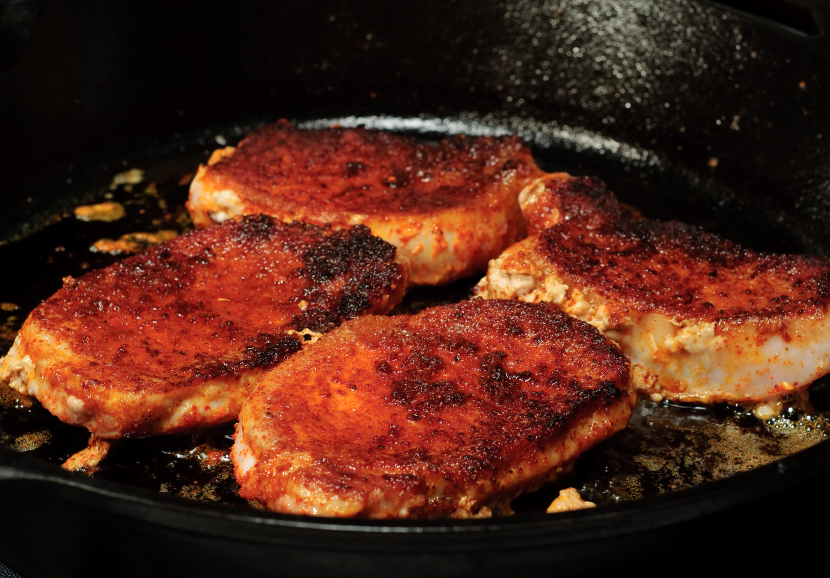 Pork chops cooking in a pan