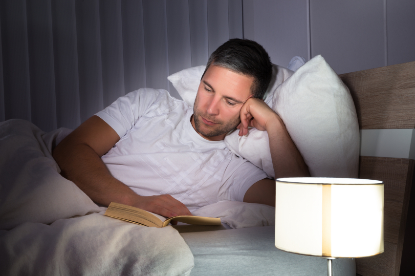 man reading in bed next to a lamp for light