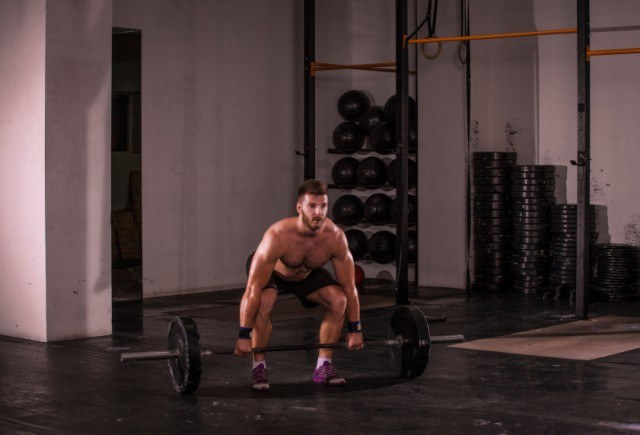 Muscular man performing deadlifts