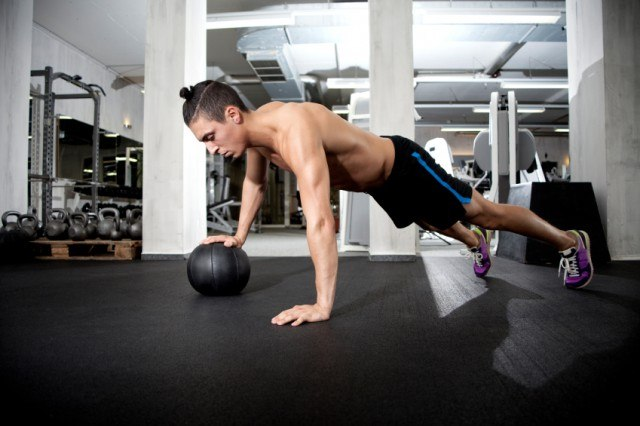 Man doing push ups with medicine ball