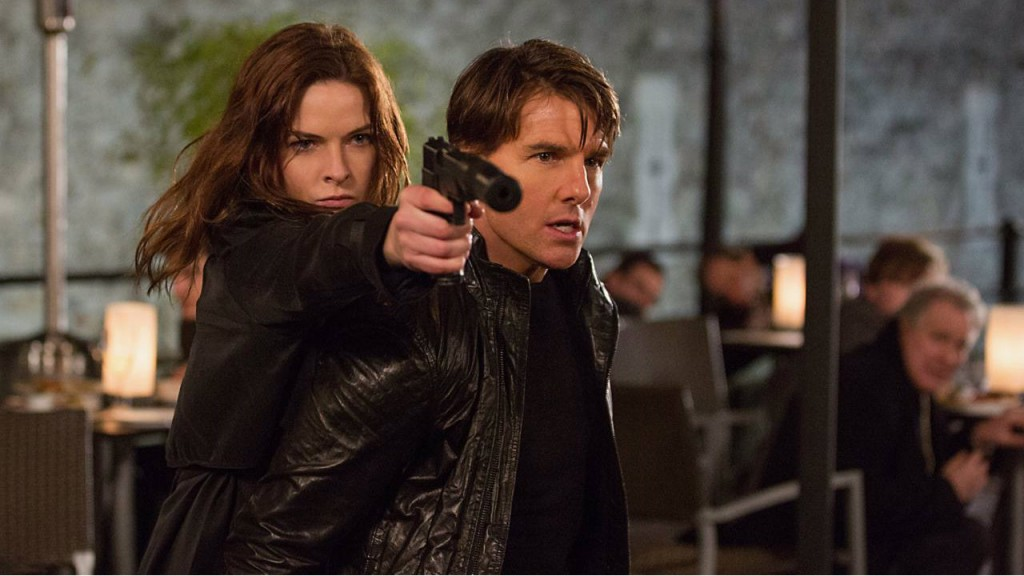 Rebecca Ferguson holding a gun and standing behind a scared Tom Cruise in Mission Impossible: Rogue Nation