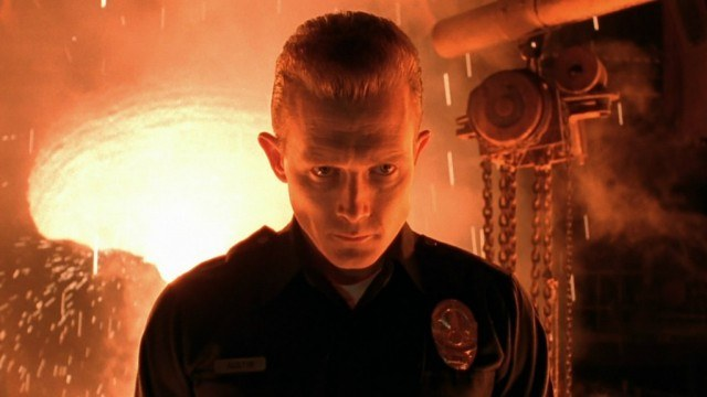 T-1000 is dressed as a policeman and is standing in front of fire.