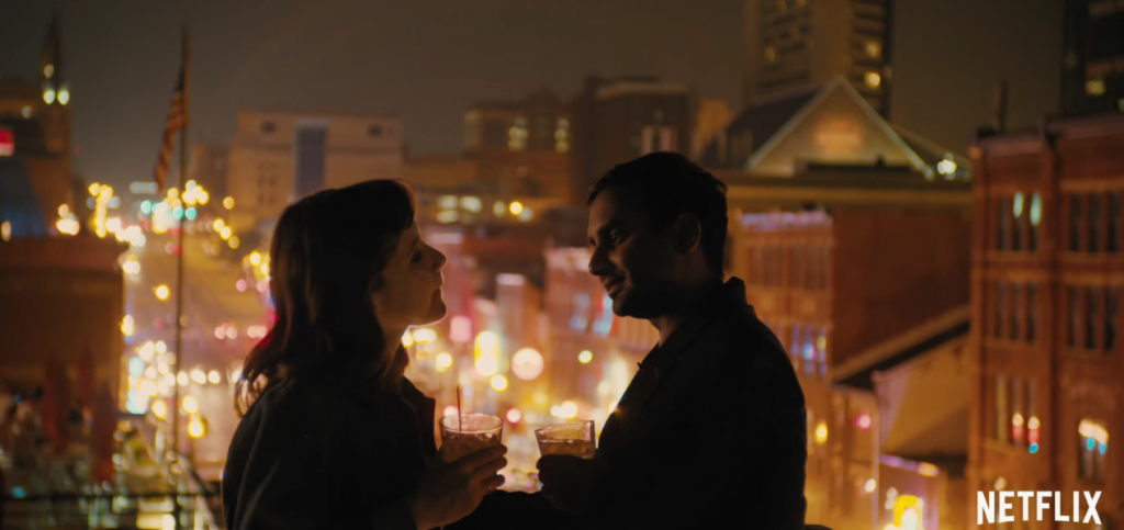 Aziz Ansari and Noël Wells stand on a rooftop at night with drinks in their hands