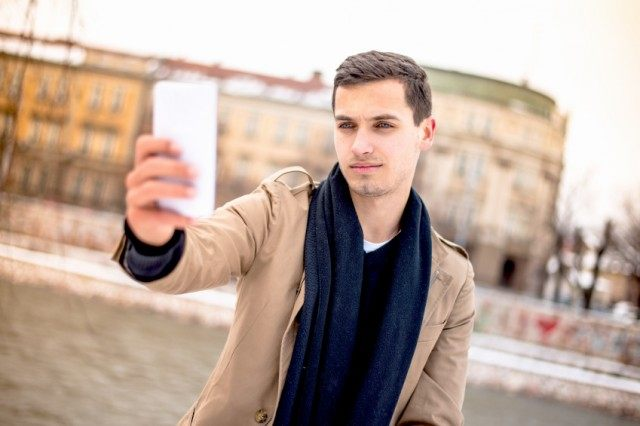 Man holding up mobile phone to take a picture.