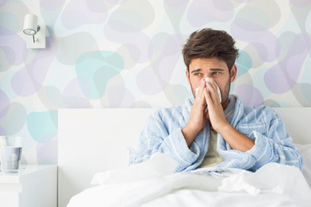 sick man blowing his nose in bed
