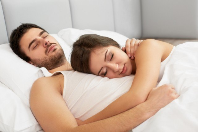 A couple laying in a bed while sleeping.