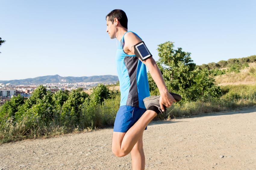 A man stretching his quadriceps after a run