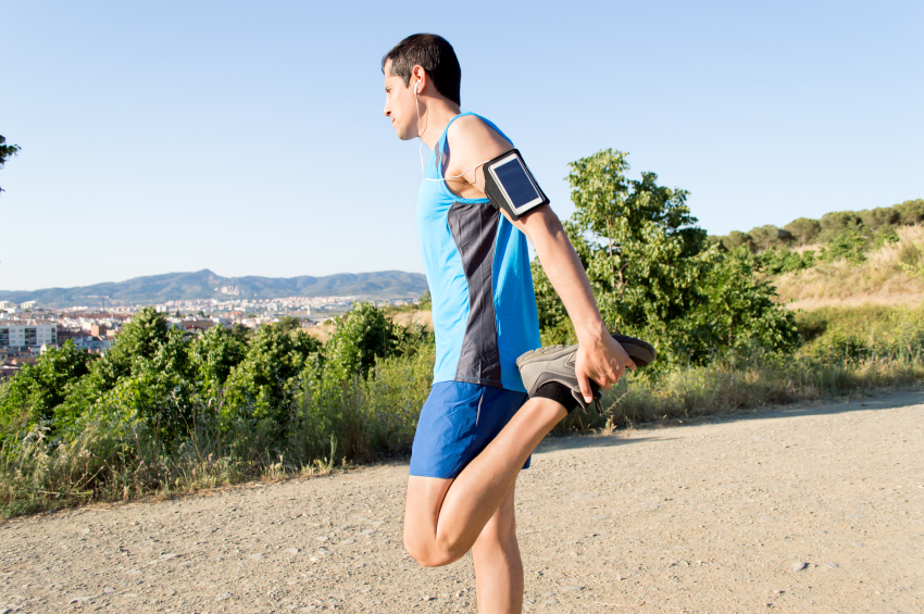 A man preparing to run, with his workout music playlist already playing
