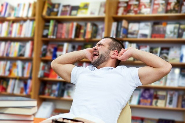 Yawning man in a library