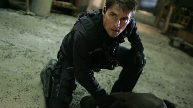 Tom Cruise kneeling down while wearing a vest.