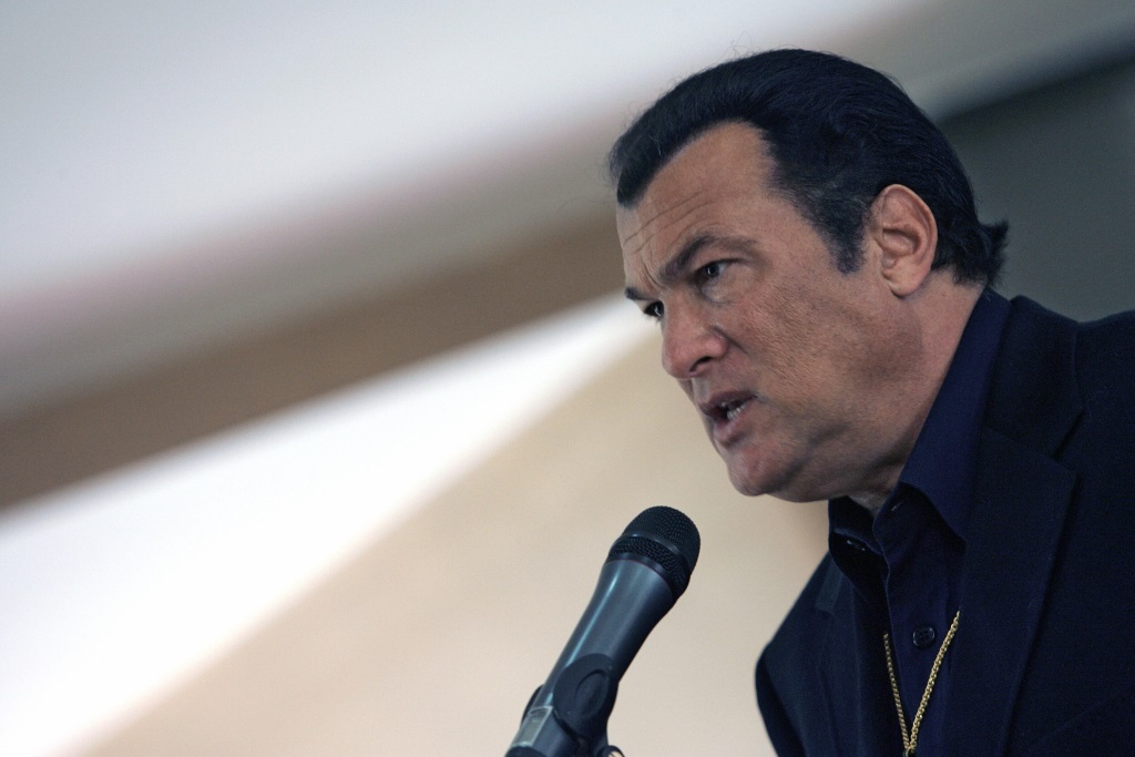 Steven Seagal is talking into a microphone.